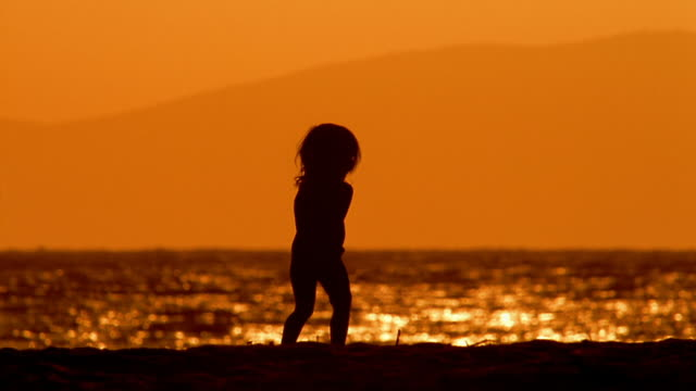 Slow motion wide shot silhouetted child walking on beach with water in background / Maui, Hawaii