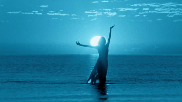 slow motion wide shot silhouetted woman walking out of water on beach at night / zoom out to long shot / mexico - controluce video stock e b–roll