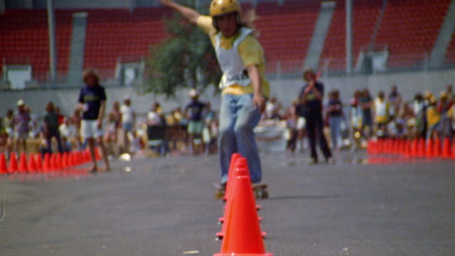 slow motion wide shot skateboarder slaloming through cones towards cam / audience in background / skateboard competition - slalom skiing stock videos & royalty-free footage