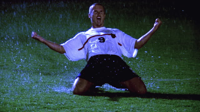 slow motion wide shot soccer player dropping to his knees, cheering + raising fist on field at night in rain