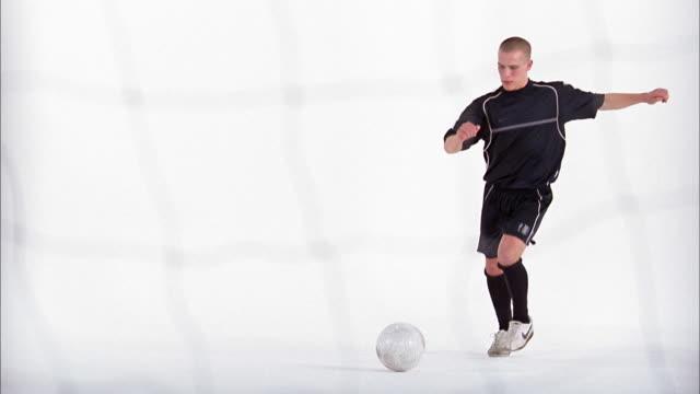 vidéos et rushes de slow motion wide shot soccer player kicking ball past diving goaltender to score goal / london - donner un coup de pied