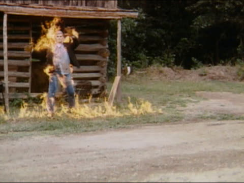1970 slow motion wide shot stunt man in protective suit on fire / audio - jeans stock videos & royalty-free footage