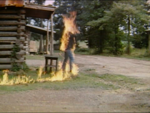 1970 slow motion wide shot stunt man in protective suit on fire / audio - stunt person stock videos & royalty-free footage