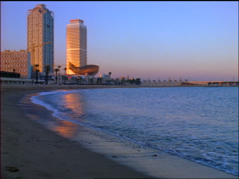 slow motion wide shot surf rolling onto beach near Hotel Arts + Torre Mapfe at dusk / Barcelona, Spain