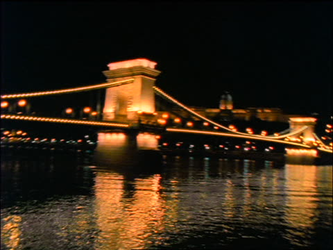 slow motion wide shot swish pans chain bridge over danube river at night / budapest, hungary - chain bridge suspension bridge stock-videos und b-roll-filmmaterial
