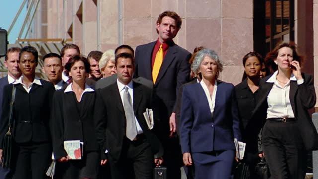 stockvideo's en b-roll-footage met slow motion wide shot tall man pushing ahead of large group of business people walking on street - opvallen in een menigte