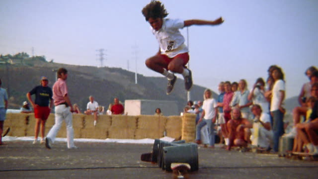 vidéos et rushes de 1976 slow motion wide shot teenage boy with long hair jumping over barrels / landing on skateboard / riding away - 1976
