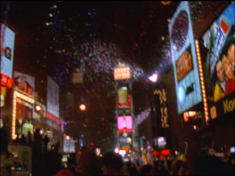 slow motion wide shot tilt down Happy New Year sign in Times Square with confetti falling + crowds / New Year's Eve, NYC
