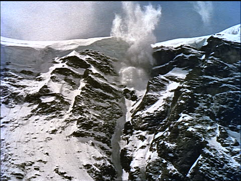 slow motion wide shot tilt down snow avalanche on rocky mountain / The Wild North (1951)