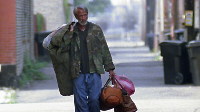 slow motion wide shot tilt up homeless man carrying several bags / walking on sidewalk - veteran stock-videos und b-roll-filmmaterial