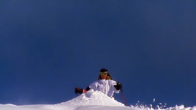 Slow motion wide shot tilt up woman skiing up mound of snow / jumping high in air / Aspen, Colorado