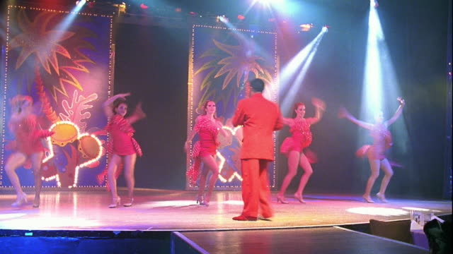 slow motion wide shot time lapse man singing on stage with female dancers / he dances with one of them