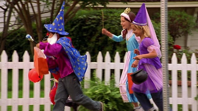 Slow motion wide shot tracking shot group of children in Halloween costumes running on sidewalk / up front walk of house