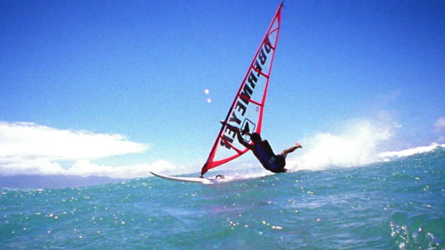 Slow motion wide shot tracking shot man windsurfing and being dragged out of control, causing wipeout / Maui, Hawaii