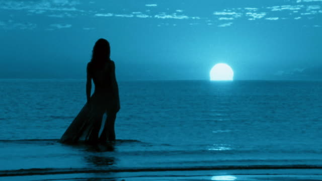 slow motion wide shot tracking shot silhouetted woman wading through water on beach at night / mexico - 謎点の映像素材/bロール