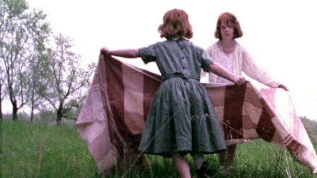 vídeos de stock e filmes b-roll de slow motion wide shot two girls spreading blanket in grass / one jumps onto blanket, they both sit / missouri - sentar se