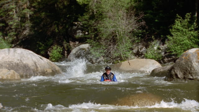 Slow motion wide shot two men jumping off rock to begin white water sledging on Roaring Fork River/ Colorado