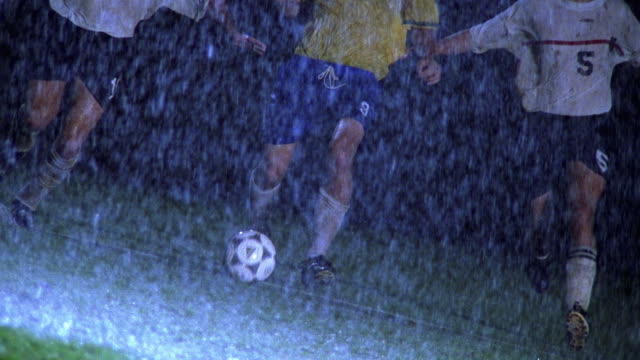 slow motion wide shot two soccer players sliding with feet to take ball from opposing player in rain at night