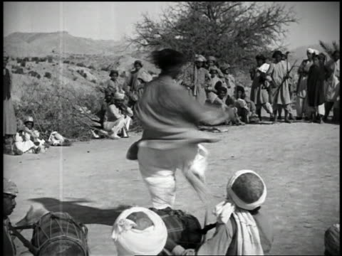 1932 slow motion wide shot waziri tribesman performing sword dance / drummers in foreground - indigenous culture stock videos & royalty-free footage
