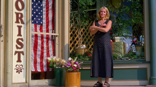Slow motion wide shot woman crossing arms next to florist shop entrance and American flag