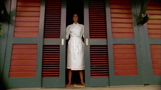 Slow motion wide shot woman in bathrobe opening sliding doors