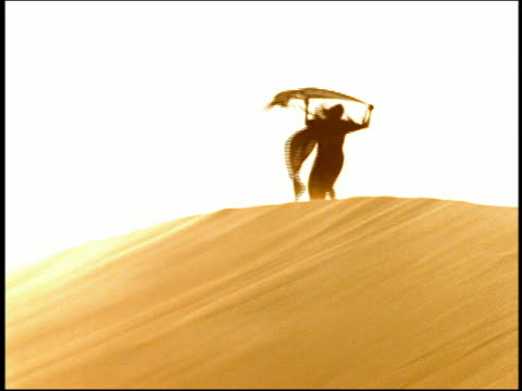 Slow motion wide shot woman in black veil walking on ridge of dune with veil and scarves blowing in wind / Egypt