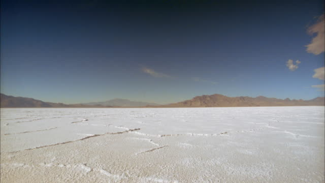 vidéos et rushes de slow motion wide shot woman running away from cam in white sand desert / salt flats, utah - utah