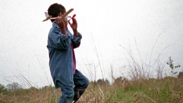 vidéos et rushes de slow motion wide shot young black boy throwing toy airplane in grassy field in rain / missouri - jetée