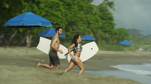 slow motion wide tracking shot of couple running to ocean on beach / esterillos, puntarenas, costa rica - 全身点の映像素材/bロール