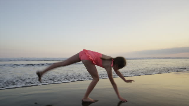 """Slow motion wide tracking shot of girl doing cartwheel on beach / Esterillos, Puntarenas, Costa Rica"""