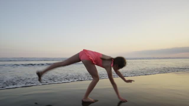 """slow motion wide tracking shot of girl doing cartwheel on beach / esterillos, puntarenas, costa rica"" - cartwheel stock videos & royalty-free footage"