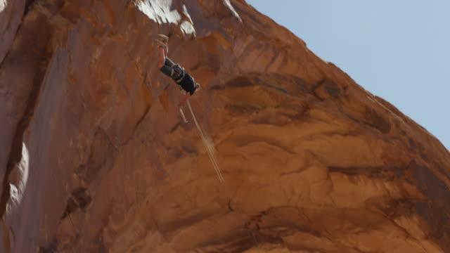 vídeos y material grabado en eventos de stock de slow motion wide tracking shot of man swinging from arch / corona arch, moab, utah, united states - puenting