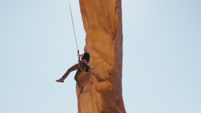 slow motion wide tracking shot of woman swinging from arch / corona arch, moab, utah, united states - abseiling stock videos & royalty-free footage