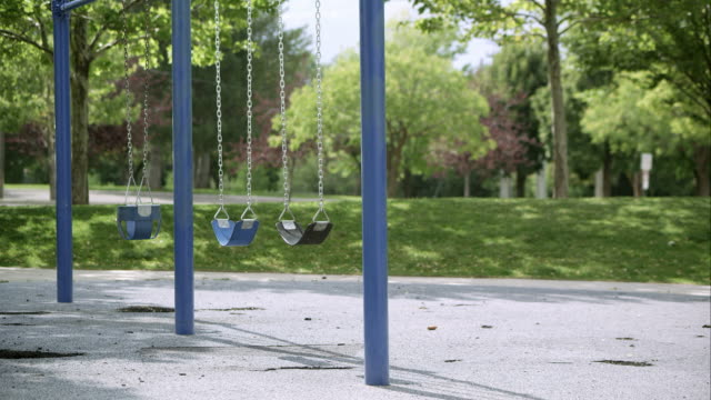 stockvideo's en b-roll-footage met slow motion wide view of swings moving in the breeze. - speeltuin