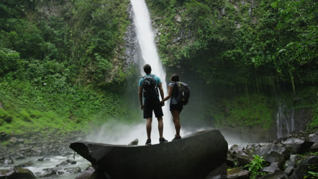 Slow motion wide zoom in of adventurous couple admiring rain forest waterfall / Arenal, La Fortuna, Costa Rica