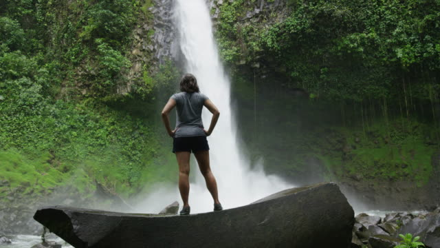slow motion wide zoom in of hiker admiring waterfall in rain forest / arenal, la fortuna, costa rica - costa rica stock videos and b-roll footage