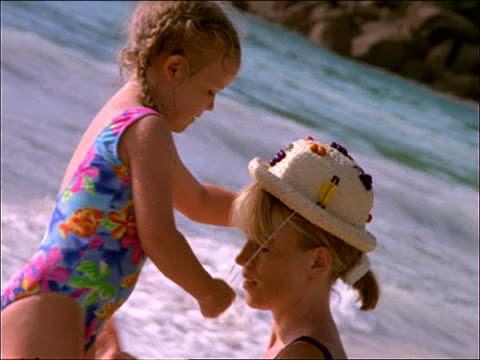 slow motion woman and small girl playing with hat in surf / kiss / seychelles - one piece swimsuit stock videos & royalty-free footage