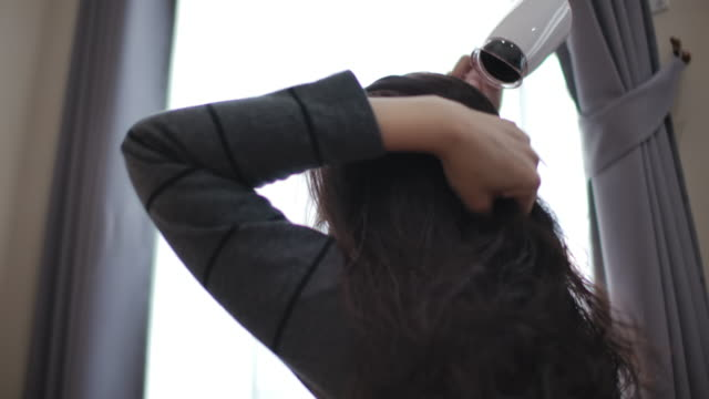 vídeos de stock e filmes b-roll de slow motion woman blow drying her hair with a hair dryer at home - toalha