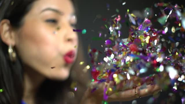 cu slow motion woman blowing confetti - confetti stock videos & royalty-free footage
