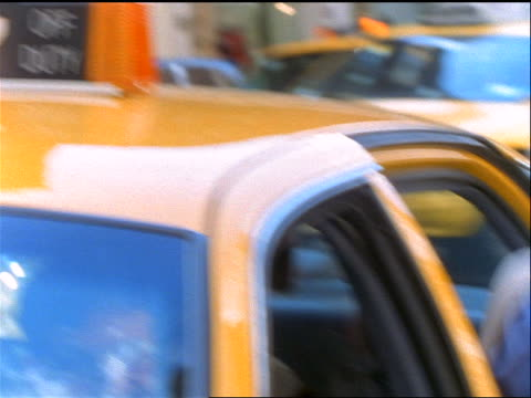 slow motion woman carrying newspaper getting out of taxi on busy nyc street - yellow taxi stock-videos und b-roll-filmmaterial