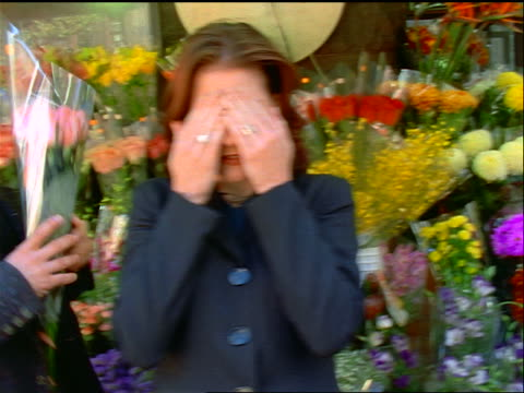 vídeos de stock, filmes e b-roll de slow motion woman covering her eyes as man hands her bouquet of roses at flower stand / they kiss - bouquet