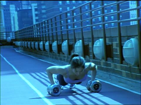 vidéos et rushes de blue slow motion pan woman doing push-ups on dumbbells on roof of building / nyc - poids pour la musculation