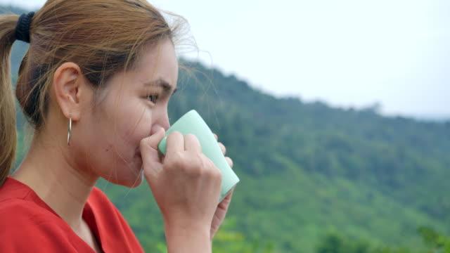 4kスローモーション、自然の景色を見ながらテラスでコーヒーを飲む女性 - 丘点の映像素材/bロール