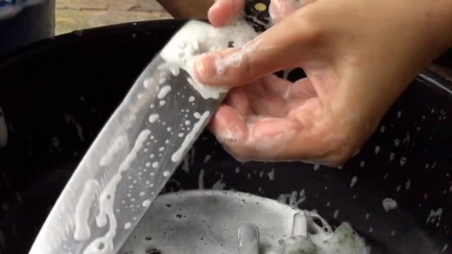 slow motion woman hand washing knife with a sponge and detergent - kitchen knife stock videos and b-roll footage