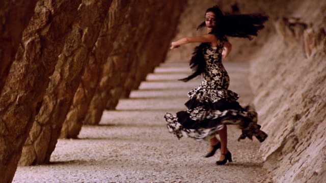 slow motion woman in flamenco dress spinning next to slanted columns in parc guell / barcelona, spain - flamenco dancing stock videos and b-roll footage