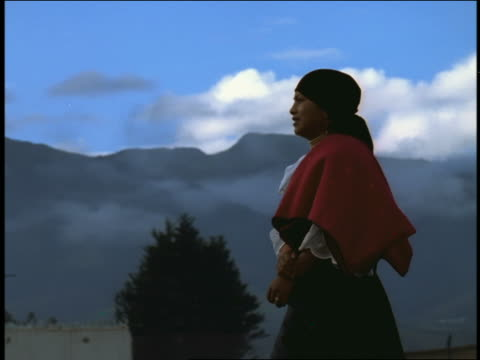 slow motion pan woman in native dress walking past camera / mountains in background / otavalo, ecuador - ecuadorian ethnicity stock videos & royalty-free footage