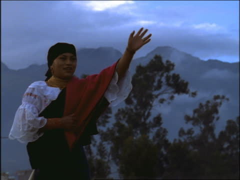 slow motion woman in native dress waving to someone offscreen / mountain in background / otavalo, ecuador - ecuadorian ethnicity stock videos & royalty-free footage