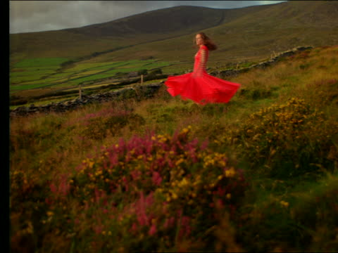 slow motion woman in red dress spinning in irish countryside - red dress stock videos & royalty-free footage