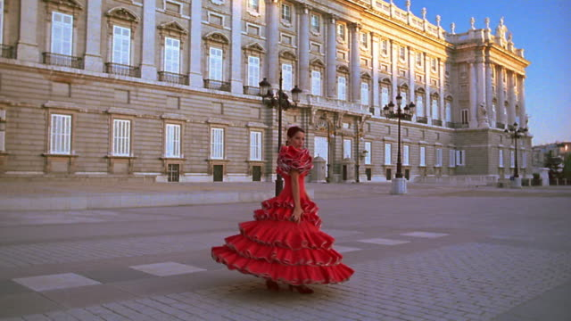 slow motion woman in red flamenco dress dancing + spinning / palacio real in background /plaza de oriente, madrid - flamenco dancing stock videos and b-roll footage