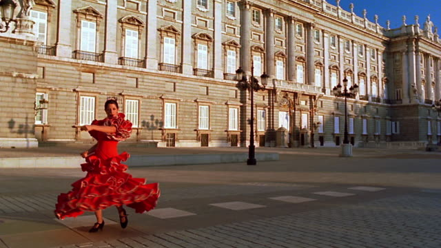 slow motion woman in red flamenco dress dancing + spinning / palacio real in background /plaza de oriente, madrid - tanzkunst stock-videos und b-roll-filmmaterial